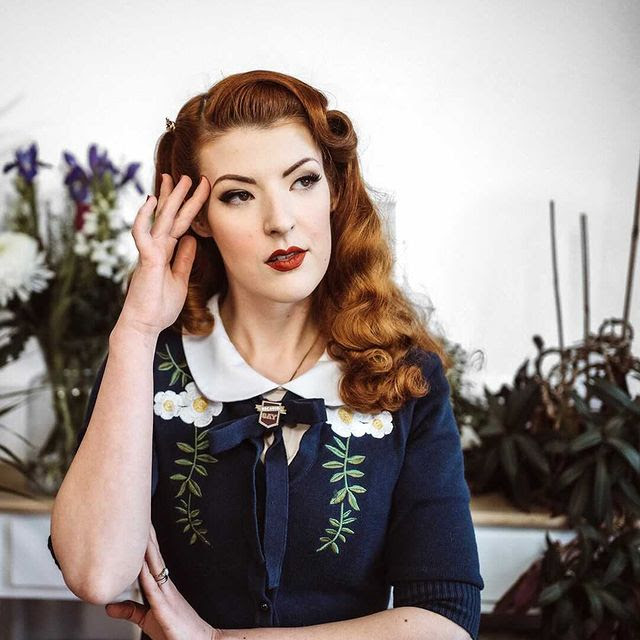 A photo of Jessica, a white woman with red hair, looking off-camera and generally looking fabulous, wearing a flowery dark blue dress with a white Peter Pan-style collar.